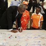 """Lagos State Governor, Mr. Babatunde Fashola, SAN (left) signing in support of the """"No To Rape"""" campaign board presented by Mirabel Centre shortly after the signing of an Executive Order Establishing a Sex Offenders' Register at the Banquet Hall, Lagos House, Ikeja, on Monday, December 1, 2014. With are: His Deputy, Hon. (Mrs) Adejoke Orelope-Adefulire (middle) and the Managing Partner, Partnership for Justice, Mirabel Centre, Itoro Eze-Anaba (right)."""