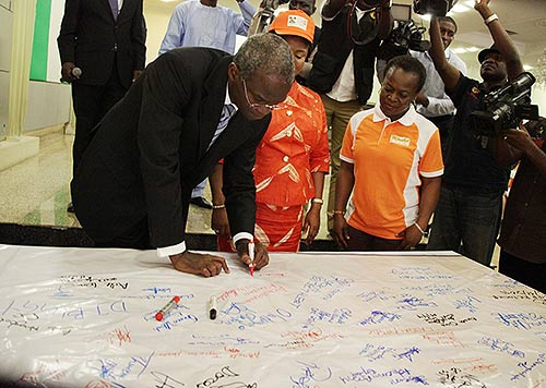 "Lagos State Governor, Mr. Babatunde Fashola, SAN (left) signing in support of the ""No To Rape"" campaign board presented by Mirabel Centre shortly after the signing of an Executive Order Establishing a Sex Offenders' Register at the Banquet Hall, Lagos House, Ikeja, on Monday, December 1, 2014. With are: His Deputy, Hon. (Mrs) Adejoke Orelope-Adefulire (middle) and the Managing Partner, Partnership for Justice, Mirabel Centre, Itoro Eze-Anaba (right)."